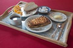 Ontbijt op een verfraaid dienblad met cake, koffie, brood, boter en sinaasappel wordt geplaatst die Stock Foto's