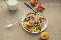 Ontbijt van de nectarine van de havermeelhavermoutpap en melkbestek stock afbeelding