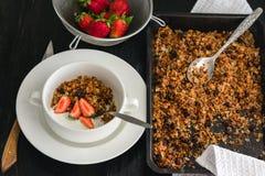Ontbijt van granola, yoghurt en aardbeien op een donkere lijst royalty-vrije stock afbeeldingen