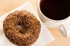 Ontbijt van koffie en chocolade verglaasde doughnut op lijst Stock Foto