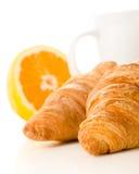 Ontbijt van verse croissants, koffie en sinaasappel over witte rug Royalty-vrije Stock Afbeeldingen