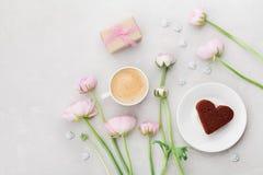 Ontbijt voor Valentijnskaartendag met hierboven kop van koffie, gift, bloemen en cake in vorm van hart op grijze lijst van Stock Afbeelding
