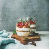 Ontbijtglazen met yougurt, granola, sinaasappel gelaagd parfait, munt royalty-vrije stock fotografie