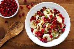 Ontbijthavermeel met granaatappel, bananen, zaden en noten Royalty-vrije Stock Foto