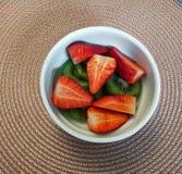 Ontbijtkom met aardbeien en kiwi op cirkeldoekachtergrond stock foto