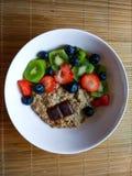 Ontbijtkom met aardbeien, kiwi, bosbes met hierboven muesli en donkere chocolade van royalty-vrije stock foto