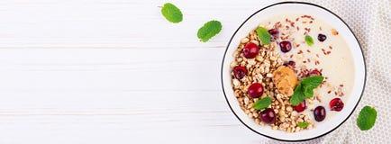 Ontbijtkom van eigengemaakte granola met fijngestampte banaan en verse bessen stock fotografie