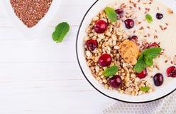 Ontbijtkom van eigengemaakte granola met fijngestampte banaan, pindakaas en verse bessen royalty-vrije stock fotografie