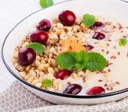 Ontbijtkom van eigengemaakte granola met fijngestampte banaan, pindakaas en verse bessen stock foto's