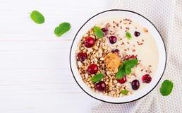 Ontbijtkom van eigengemaakte granola met fijngestampte banaan, pindakaas en verse bessen T stock afbeeldingen
