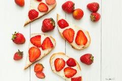 Ontbijtlijst, de gehele toost van het tarwebrood met aardbei en boter op houten lijst, hoogste mening royalty-vrije stock foto