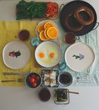 Ontbijtlijst met ongezuurde broodjes, sinaasappelen en andere verse groenten stock afbeelding