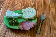Ontbijtplaat met prosciutto, olijven, wit kaas en brood Stock Foto's