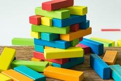 Ontbreek en doe ineenstorten binnen kleurrijke houten bloktoren als Risico of steek royalty-vrije stock foto's