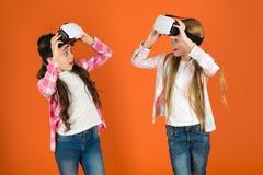 Ontdek virtuele werkelijkheid De jonge geitjesmeisjes spelen virtueel werkelijkheidsspel De vrienden werken in vr op elkaar in On stock afbeeldingen