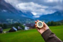 Ontdekkingsreiziger die richting met kompas in de zomerbergen, p zoeken stock foto's