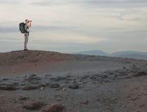 Ontdekkingsreiziger met binoculaire onderzoeken iets in een woestijn stock afbeelding