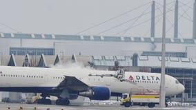 Ontdooiend Delta Airlines in de Luchthaven van München, sneeuw stock footage