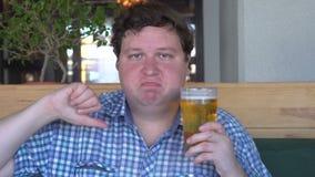 Ontevreden jonge mens die een glas bier houden en duim neer tonen stock videobeelden