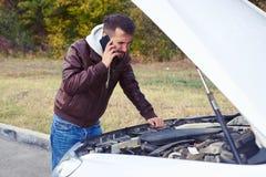 Ontevreden mens die onder de kap van analyseauto kijken stock foto's