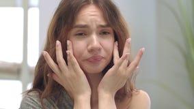 Ontevreden vrouw wat betreft gezichtshuid in badkamersspiegel Het concept van de probleemhuid stock footage