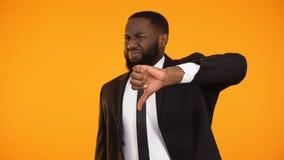 Ontevreden zwarte zakenman die duim-onderaan gebaar, de slechte kwaliteitsdienst maken stock footage