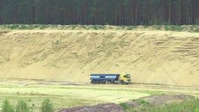 Ontginnend dagbouwextractie van de bouw van geel zand, verwoesting en degradatie, een vrachtwagen met een aanhangwagen stock footage