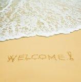 Onthaal dat in een zand wordt geschreven Royalty-vrije Stock Foto's