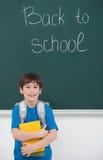 Onthaal terug naar school! Vrolijk weinig schooljongen die BO houden stock foto