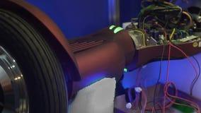 Ontmantelde segway in reparatiewerkplaats, wiel het spinnen, die het werk capaciteit controleren stock videobeelden