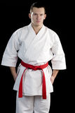 Ontrast karate young fighter on black. High Contrast karate male fighter on black background Royalty Free Stock Photo