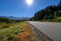Ontruim blauwe die hemel op een lege weg op de Canadese grens van de V.S. wordt gezien stock fotografie
