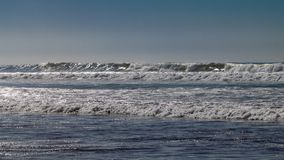 Ontruim blauwe hemel en zonlicht met de golven die van de Atlantische Oceaan op zandstrand verpletteren zonder mensen in Agadir,  royalty-vrije stock foto