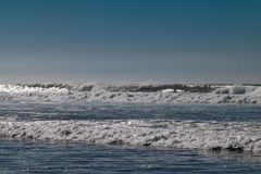Ontruim blauwe hemel en zonlicht met de golven die van de Atlantische Oceaan op zandstrand verpletteren zonder mensen in Agadir,  stock foto
