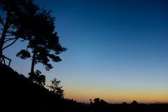 Ontruim blauwe hemel na zonsondergang die kijkend van gesilhouetteerde mou stock foto