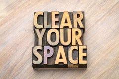 Ontruim uw ruimte - woordsamenvatting in houten type stock foto's