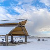 Ontruim Vierkant Expansief landschap dat met onder sneeuw onder een bewolkte blauwe hemel in de winter wordt bedekt stock foto