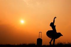 Ontspan Aziatische vrouw met een koffer op een weide bij zonsondergangsilhouet Het concept van de vakantiereis Stock Afbeelding