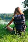 Ontspan de zitting van de vrouwenreiziger op het gras Royalty-vrije Stock Fotografie