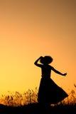 Ontspan genieten van vrouw en zonsondergangsilhouet Stock Afbeeldingen