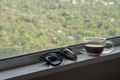 Ontspan met koffie door het venster stock fotografie