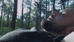 Ontspan op een hangmat Een jonge mens met een baard ligt op een hangmat in een park onder de bomen Een slaapmens op een hangmat stock videobeelden
