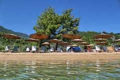 Ontspan op het aardige strand met zonparaplu's en zonbedden Stock Fotografie