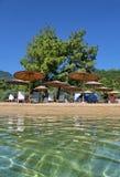 Ontspan op het aardige strand met zonparaplu's en zonbedden Stock Afbeelding