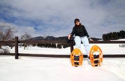 Ontspan van vrouw met sneeuwschoenen in de sneeuw tijdens de winterholi Stock Afbeeldingen