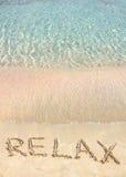 Ontspan woord in het zand, op een mooi strand met duidelijke blauwe golven op achtergrond wordt geschreven die Royalty-vrije Stock Afbeelding