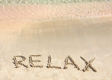 Ontspan woord in het zand, op een mooi strand met duidelijke blauwe golven op achtergrond wordt geschreven die Stock Afbeelding