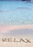 Ontspan woord in het zand, op een mooi strand met duidelijke blauwe golven op achtergrond wordt geschreven die Stock Fotografie