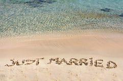 Ontspan woord in het zand, op een mooi strand met duidelijke blauwe golven op achtergrond wordt geschreven die Royalty-vrije Stock Fotografie