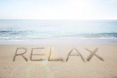 Ontspan woord met de hand geschreven in zand op zonnig strand Stock Foto's